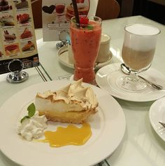 lemon merringue pie with blended orange strawberry pineapple and hot latte. #merringue #pie #lemon #smoothie #fruit #healthy #latte #hot #drink #sweet #yummy #tasty #delicious #sour #coffee #cafe #coffeeshop
