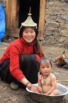 Bhutan - Mother bathing baby in tin tub.