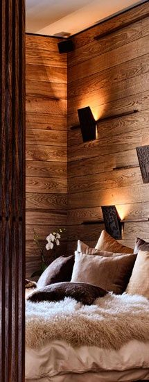 Cozy bedroom with amazing lighting, textured reclaimed wood and fur blankets...sign me up right now.