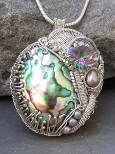Can you believe this piece started with the idea that the concave faceted 16mm. Mystic Topaz and the Abalone cabochon needed to be together? That was the starting point, and over a period of about a month, this tour-de-force of wirework artistry came to be. Its about 2 3/4 long and 2 wide and about 1 deep. Its HUGE ! And HEAVY! It will not fail to draw attention, so if you are shy, this may not be the piece for you!