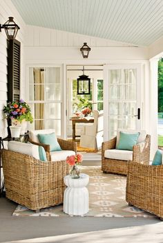 Warm wicker, ivory cushions, pale blue acccent pillow, beige/ivory rug, side table with potted flowers. Black light fixtures. No center table.