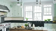 For a new kitchen in Mount Kisco, New York, Shaker-style cabinets by Plain & Fancy, painted Teresa's Green by Farrow & Ball, have a wonderfully old-fashioned but surprisingly fresh look. Vintage pendants hung at different heights provide ambient and task lighting. The dark brass schoolhouse lights were found at Scherer's Architectural Antiques.   - HouseBeautiful.com