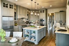 We've crafted the #kitchen of your dreams, compete with elegant #green #cabinetry, #granite #countertops, charming #hardwood #floors, and warm lighting. #interior #design #home #decor #luxury