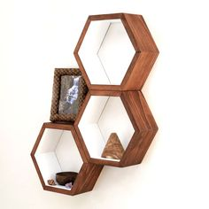 """Hang these on a wall, fill them with charming knickknacks, and """"bee"""" a trendsetter with these honeycomb-shaped shelves. Walnut-toned wood exteriors and creamy interiors offer a contemporary spin on a mid-century look."""