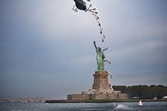 20. August, New York: Werbung für den fünften Stopp der Red Bull Cliff Diving World Series. Der Kolumbianer Orlando Duque springt aus einem in etwa 23 Metern Höhe schwebenden Helikopter an der Freiheitsstatue in New York vorbei in den Atlantik (Aufnahme aus mehreren Belichtungen). Foto: dpa  Weitere Bilder des Tages: www.noz.de/74175301