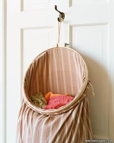 oh, that martha stewart. she solved my problem again. i just love you, marth! hanging laundry bag made from embroidery hoop and a pillowcase. (or existing laundry bag.)