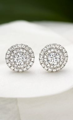 Dazzling round diamonds are encircled by two halos of scalloped pavé set diamond accents in these glamorous earrings.