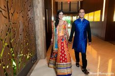 An Indian bride and groom celebrate at their colorful sangeet.