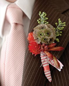 Groomsmen's boutonnieres combine flowers found in the bride's bouquet, like scabiosa and eucalyptus fruit, and are bound in red-and-white seersucker.