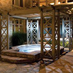 WOOD PERGOLA KIT: Unique Pergola over a raised stone hot tub on a stone patio. Great pergola kit.