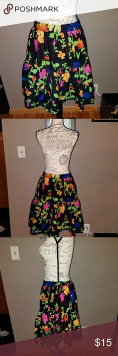 Old Navy Vibrant Floral Skirt This skirt is very flowy and comfortable. It is 100% cotton with an orange lining underneath. There are many colors of flowers (green, yellow, pink, blue, orange) on a black background. The waist is 19 inches across unstretched and it is 22 inches long. The waist is elastic. There is a ruffle about halfway down for extra movement and volume.  Thank you for looking and please check out my other items! Old Navy Skirts A-Line or Full