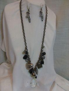 Hermoso collar de 80 cm. de largo elaborado con cristales facetados, perlas de cristal, dijes metálicos, cristal de 4 cm en forma de gota, y ganchos de plata.