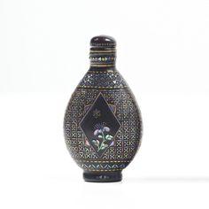 JAPON - XIXe siècle  Flacon tabatière de forme ovale en laque noir burgautée à décor central sur chaque face d'un médaillon losangé fleuri, et de frises géométriques de fleurs. Marque Qianli.