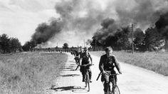 Suomalaiset sotilaat perääntymässä Äänislinnasta (Petroskoi). Polkupyöräjoukkoja tiellä, asemaparakit palavat tien vieressä. SA-kuva.