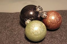 Clear ornaments, baby oil, and glitter. Put baby oil in the ornaments, coat the insides then drain excess. Add glitter, and voila! No mess glitter ornaments.