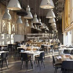 Industrial lights over a kitchen island?Industrial outdoor lamps hang over the tables of a restaurant in Tel Aviv by Israeli architects Baranowitz Kronenberg
