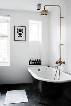 A classic monochrome bathtub with a striking gold shower fixture - timeless!