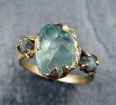 Raw Uncut Aquamarine Diamond Gold Engagement Ring Wedding Ring Custom One Of a Kind Gemstone Ring Bespoke Three stone Ring byAngeline Raw rough aquamarine surrounded by two raw conflict free diamonds. I hand carved this ring in wax and cast it in solid 14k gold using the lost wax casting process. This one of a kind raw gemstone ring is a size 5 1/2 it can be sized. The aquamarine stone measures about 9mm X 8mm. The rough diamonds are about 3mm. I do have more gemstones and can create ...