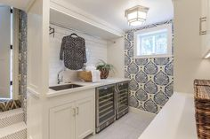 David Duncan Livingston Photography - Beautiful blue and white sunken laundry room is equipped with side-by-side mini wine fridges enclosed beneath a white countertop accenting white cabinets fitted with nickel pulls and a stainless steel sink paired with a polished nickel faucet.