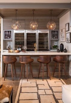 Three Arteriors Beck Pendants illuminating a marble waterfall bar fitted with a wet bar sink and gold gooseneck faucet lined with wood counter stools.