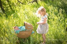 """Newborn in an antique doll carriage """"pushed"""" by big sister."""