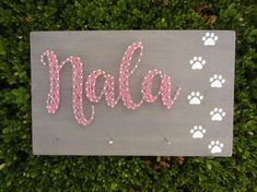 "A decorative and functional string art for your wall. This piece comes with 3 nails to hang your dog leashes and other accessories on. You can personalize it with your dogs name. {Measurements}: 9.25"" X *Depends on length of name* {Add-ons}: 3 nails along the bottom to hang dog"