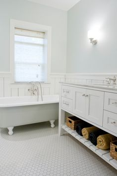 Lovely ensuite bathroom with bue green walls paint color, chair rail with wall panels groove walls, vintage clawfoot tub, benjamin Blackwelder white bathroom vanity with marble counter top, hexagon tiles floor and polished nickel faucet and hardware.