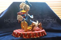 Celebrate the life of everyone's favorite quarrelsome duck with this exclusive Donald Duck Chip n Dale statue!  This figurine is Limited in production and exclusive to only Disney Parks, our amazingly detailed feathered friend is replicated in larger-than-life detail in a scene depicting the furry duo of Chip'n'Dale mischievously taking the ice cream of a dumbfounded Donald.