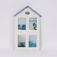 """This Beach hut photoframe has a cream wooden panel effect in the shape of a beach hut and finished off with a blue roof.  This photoframe holds four 6"""" x 4"""" photographs."""