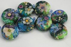 Series of handmade glass beads using many layers of glass to give the appearance of a miniature watercolor painting.