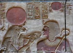 """'Seti and Sekhmet at Abydos.' This relief shows the lion-headed goddess Sekhmet holding the """"ankh"""" sign before the mouth of pharaoh Seti I. The sign is entwined in her """"menat"""" necklace. Dynasty 19"""