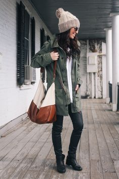 Sydney is wearing skinny black pants and boots, hunter green jacket, grey chunky beanie, and Mishqua canvas and leather duffle bag (from The Daybook)