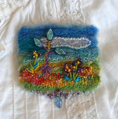 This glistening little landscape brooch shimmers with light and whimsy. Lovely soft shades of periwinkle and cerulean blue fade surround a fluffy cloud complete with silver lining. Splashes of sunny yellow, orange, crimson and sparkling raspberry sparkle and glow. The grasses and foliage are created with layers of needle felted wool and silk roving. Pretty leaf beads wave on stems of tiny bullion knots and silk ribbon stitches. A dainty swag created with glass beads adorns the bottom edge…