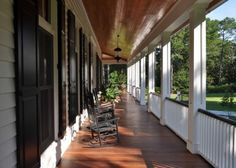 """Yes, Please!  """"Here's a close-up of the Lowcountry porch, complete with lovely railings, traditional shutters, windows with transoms, lovely lighting, plants and beautiful wood underfoot and overhead. One of the best ways to make sure your porch is at its most welcoming is to add plenty of comfortable rocking chairs."""""""