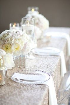 i love everything about this reception table look! sparkling silver tablecloth + white peonies + clear glass plates + floating candles