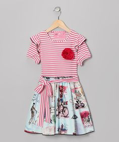 Any charming chickadee will love this frock that flaunts a striped sash around the waist and a stretchy fit for comfort. An enchanting Paris scene on the skirt and ruffled sleeves add an extra bit of flair and fanciness.Bodice: 95% cotton / 5% spandexSkirt: 100% cottonMachine wash; tumble dry