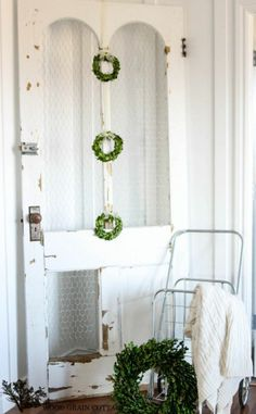 Use an old antique door for decoration. Hang wreaths on the door and lean against a wall.