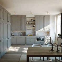 Shaker style kitchen, soft grey painted cabinetry, mix of Shaker doors and flat-fronted doors, small doorknobs, discreet sink and hob area.  Lovely & elegant.