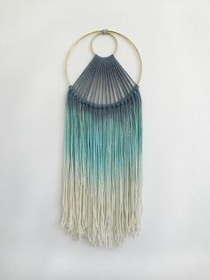 This wall hanging is hand made with cotton cording and hand dyed in beautiful blues to create an ombre effect. Earthy and cheerful to brighten up any space!  Overall Length: 19 (49cm) Outer Hoop Diameter: 7 (18cm) Smaller Inner Hoop Diameter: 2 (5cm)  Markota1970 is my collection of hand-made jewelry and weavings. I am inspired by materials, having long had a love of fibers, textiles and natural stones. I find inspiration in the style of the 70s as much as the adornments of indigenous…