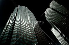 low angle shot of office building at night. - Low angle view of a tall commercial building against sky at night.