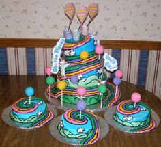 Dr. Seuss' Oh, the Places You'll Go Birthday Cake with Smash Cakes: This cake was for a set of triplet's first birthday. The balloon baskets and babies were made out of Chocolate Candy Clay.  The edible balloons were Cake Pops that were frosted and rolled in Sanding Sugar