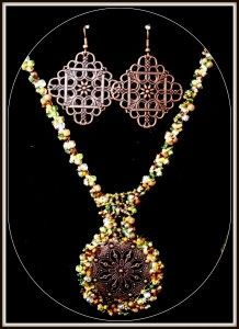 beaded rope necklace around a bronze filigree with filigree earrings. bottle green, amber and copper colors