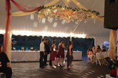 white lattice with artificial roses and hanging globes with led tealights over a dance floor in a reception tent at Apple Blossom Chapel and Gardens