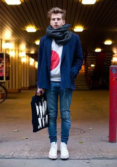 Shop this look on Lookastic:  http://lookastic.com/men/looks/scarf-crew-neck-sweater-double-breasted-blazer-tote-bag-skinny-jeans-low-top-sneakers/7624  — Charcoal Knit Scarf  — White and Red Print Crew-neck Sweater  — Navy Double Breasted Blazer  — Navy and White Print Canvas Tote Bag  — Blue Skinny Jeans  — White Low Top Sneakers