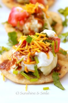 Indian street food which has crisp fried dough wafers covered with plain yogurt, some boiled potatoes, tangy tamarind chutney, spicy green chutney and then, topped with some onion, tomatoes and  cucumber