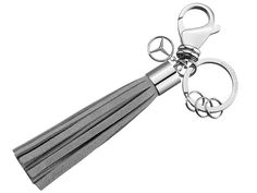 B66953830  The appeal of this special key ring lies in its high-quality details.  The elegant grey suede tassel combines with the high-sheen stainless steel fittings to optimum effect.  And the small, decorative charm in the form of an openwork 3D star logo subtly harmonises with the overall look.  The key ring features a flat split ring with three mini split rings, making it easy to remove or replace individual keys. Cannes, Mercedes Benz, Special Keys, Benz Amg, Stainless Steel Fittings, 3d Star, Star Logo, Split Ring, Key Rings