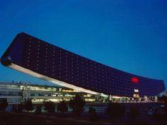 """Sanyo Solar Arc Essa estrutura em forma de asa elegantemente """"pousada"""" no solo abriga desde 2002 o Museu da Energia Solar, mais conhecido como Sanyo Solar Ark. Semelhante a um arco de 315 metros de largura e 37 m de altura. Localizado na Província de Gifu, no centro do Japão, o impressionante edifício possui mais 5 mil paineis solares e produz mais de 500 mil kWh de energia por ano. A fachada da atração, que também abriga centro de pesquisa em tecnologia solar da Sanyo, também é coberta por…"""