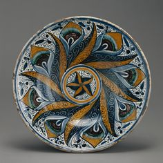Title: Dish with a Peacock Feather Pattern  Artist/Maker(s): Unknown  Culture: Italian  Place(s): Deruta (probably), Italy (Place created)  Date: about 1470 - 1500  Medium: Tin-glazed earthenware  Dimensions: 6.4 x 39.1 cm (2 1/2 x 15 3/8 in.)