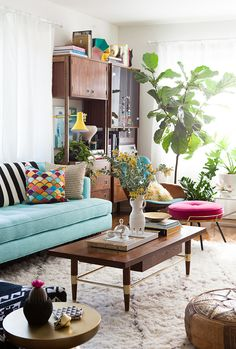 Fun mid-century modern living room with turquoise sofa and indoor plants.