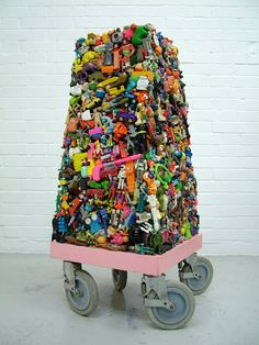 """Wayne Chisnall, """"Magnet"""", sculptural plinth comprised of both souvenir and contemporary toys. This piece was originally titled """"Toy Tower"""", but the name was changed when the artist first exhibited this work, as he realized it had amazing powers of attraction on both kids and adults alike."""